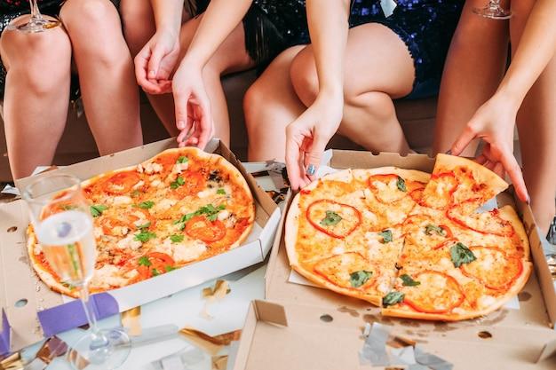 Festa corporativa. foto recortada de senhoras em minissaias sentadas, comendo pizza, bebendo champanhe.