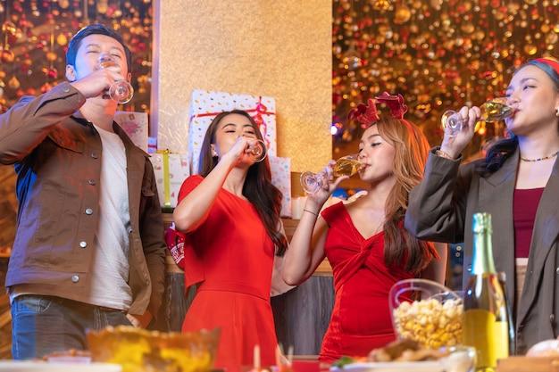 Festa da linda amiga asiática feminina e masculina comemorando a felicidade natal comemorar o jantar