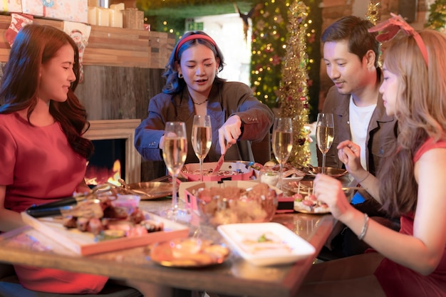 Festa da linda amiga asiática feminina e masculina comemorando mulher servindo pizza na mesa