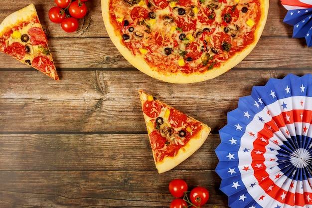 Festa da pizza para o feriado americano na mesa de madeira.