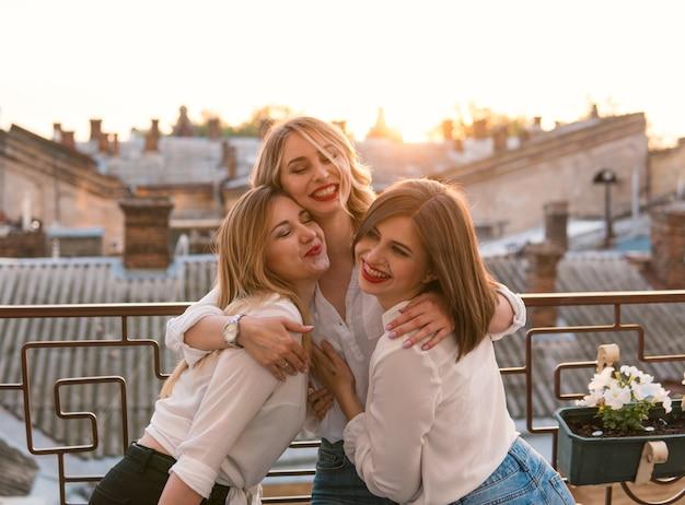 Festa das meninas. amizade de mulheres bonitas na varanda ou telhado na despedida de solteira durante o pôr do sol. eles estão se abraçando