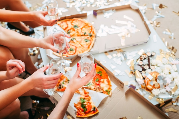 Festa das meninas. foto recortada de mulheres conversando, sentadas em frente a uma pizza em caixas, segurando taças com champanhe.