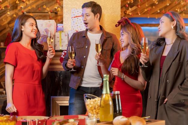 Festa de amigos asiáticos curtindo bebidas de natal e comemorando fechar copos de tilintar