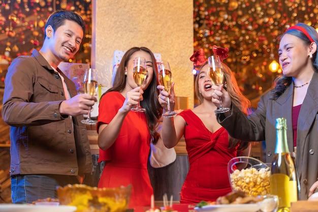 Festa de amigos asiáticos curtindo o natal, comemorando fechar copos de taças tilintando