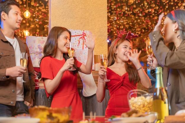 Festa de amigos asiáticos femininos e masculinos celebrando a felicidade dos amigos na véspera de natal celebrando o jantar