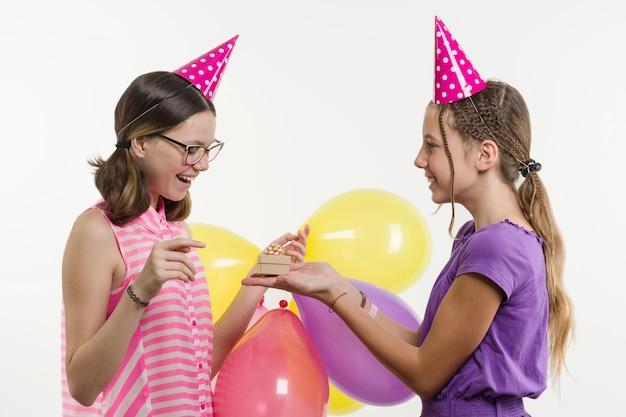 Festa de aniversário. adolescentes meninas dão um presente.