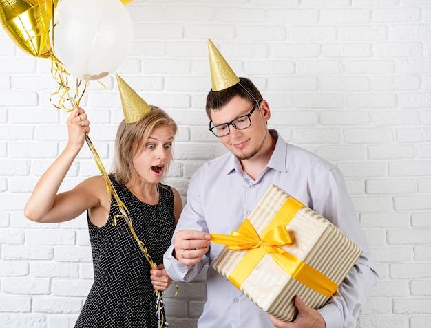 Festa de aniversário. casal jovem engraçado comemorando aniversário abrindo uma grande caixa de presente sobre fundo de tijolos brancos