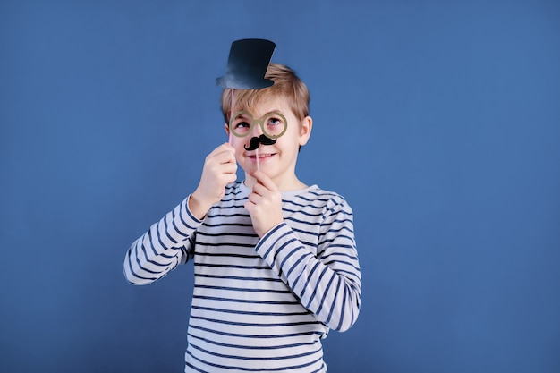 Festa de aniversário e menino com óculos em chapéus e adereços na parede azul