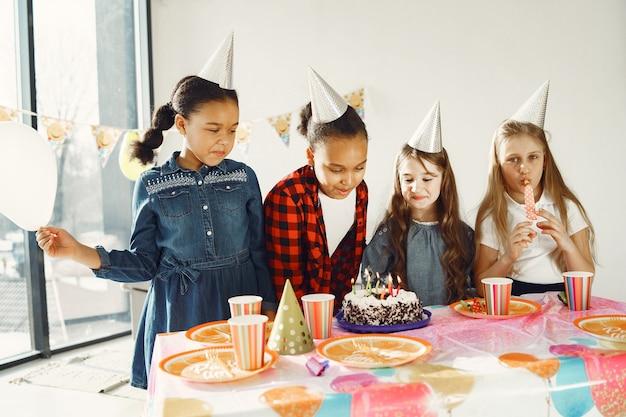 Festa de aniversário engraçada infantil no quarto decorado. crianças felizes com bolo e balões.