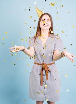 Festa de aniversário. garota tennager usando um chapéu dourado de aniversário soprando confete sobre o fundo azul