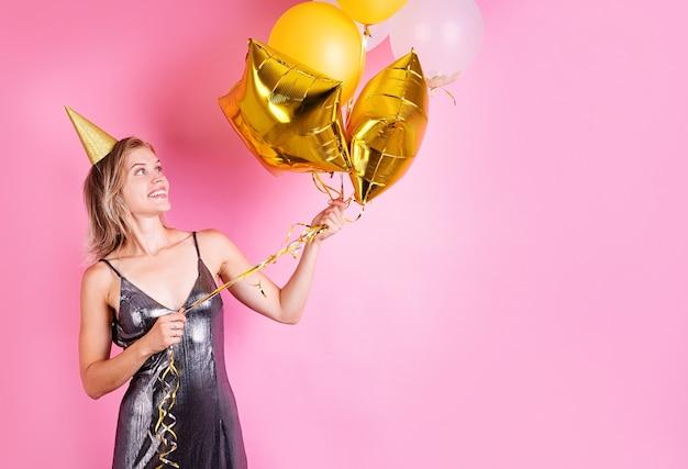 Festa de aniversário. jovem loira sorridente usando um chapéu de aniversário segurando balões dourados comemorando o aniversário em um fundo rosa com espaço de cópia