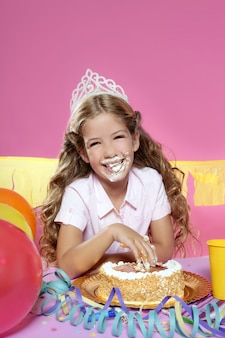 Festa de aniversário loira pequena girleating bolo com as mãos