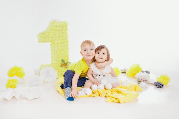 Festa de aniversário: menina e menino sentado no chão entre a decoração: números 1, flores artificiais e bolas brancas