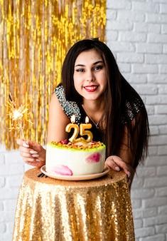 Festa de aniversário. mulher caucasiana atraente em vestido de festa preto pronta para comer bolo de aniversário comemorando seu vigésimo quinto aniversário