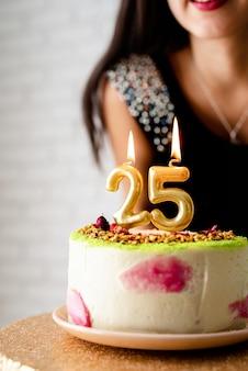 Festa de aniversário. mulher caucasiana em vestido de festa preto acendendo velas no bolo de aniversário