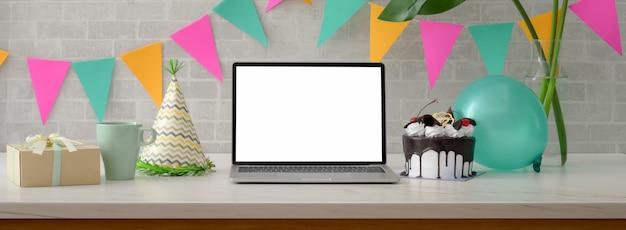 Festa de aniversário online com laptop de tela em branco, bolo, chapéu de festa e decorações