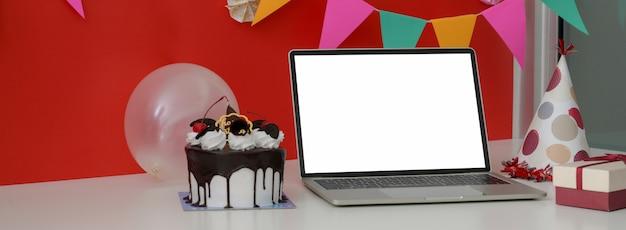 Festa de aniversário online com laptop de tela em branco, bolo e balão na mesa branca