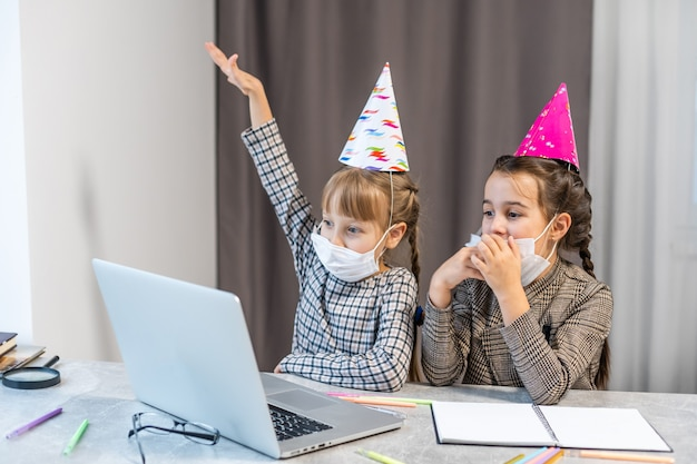 Festa de aniversário online para crianças. meninas de vestidos e chapéu celebram o feriado com amigos. conferência, videochamada em laptop