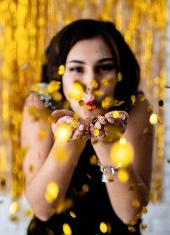 Festa de aniversário. retrato de uma jovem linda soprando confete dourado na festa de natal