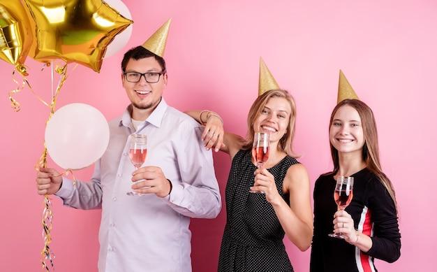 Festa de aniversário. três amigos com chapéus de aniversário bebendo vinho e comemorando a festa sobre fundo rosa