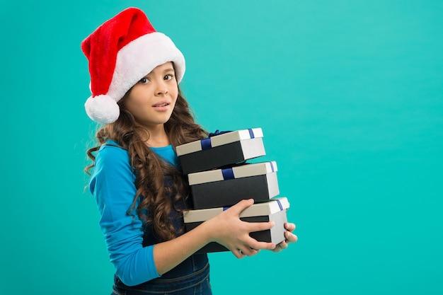 Festa de ano novo. criança de papai noel. menina com chapéu de papai noel. presente para o natal. infância. boas férias de inverno. menina pequena. compras de natal. feliz ano novo 2019. copie o espaço.
