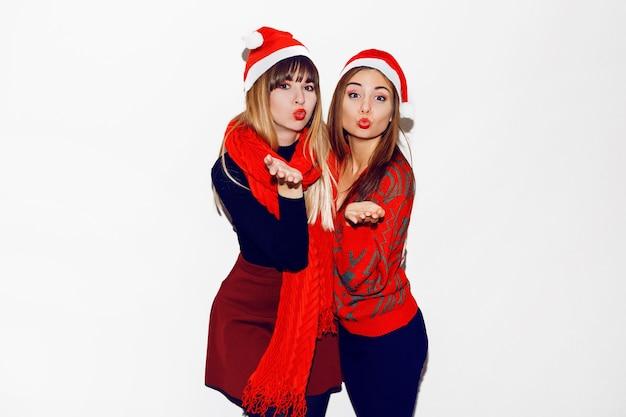 Festa de ano novo. duas lindas garotas com chapéus engraçados de papai noel mandam beijo. imagem de estoque interno de melhores amigos posando. isolar.