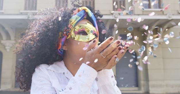 Festa de carnaval. mulher brasileira de cabelo encaracolado em traje soprando confete.