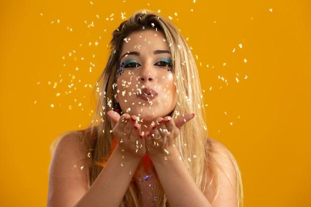 Festa de carnaval. mulher de cabelo encaracolado brasileiro em traje soprando confete