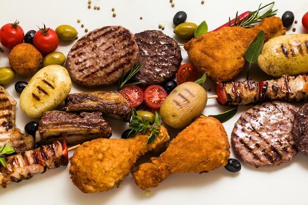 Festa de carne para churrasco com diferentes tipos de carne: hambúrgueres de carne, costelinha de porco, almôndegas de peru, coxas de frango à milanesa com batatas e tomates, temperos e ervas aromáticas. menu de verão