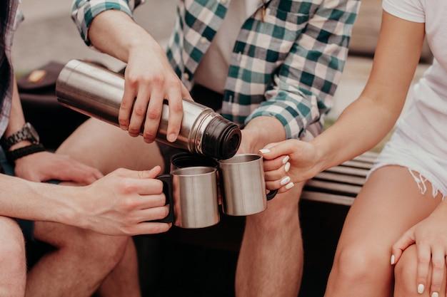 Festa de chá na rua. três jovens estudantes derramam chá de uma garrafa térmica em copos, sentado em um banco.