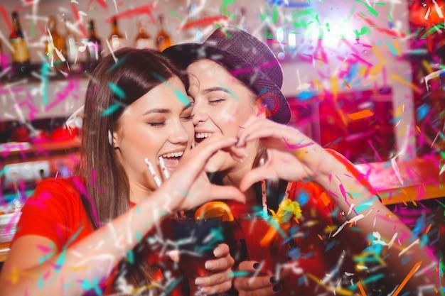 Festa de confetes. duas jovens lésbicas fazem um coração com as mãos em uma festa do clube