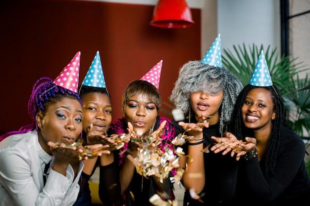 Festa de confetes. feliz jovem grupo africano de pessoas comemorando o ano novo e soprando confetes