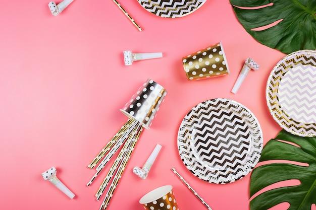 Festa de copos de papel dourado e prateado, pratos e canudos, chifres de festa e folhas de monstera em uma mesa.