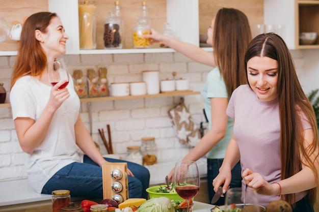 Festa de cozinha de meninas. comunicação de amigos. lazer divertido. mulheres bebendo vinho e conversando enquanto cozinham