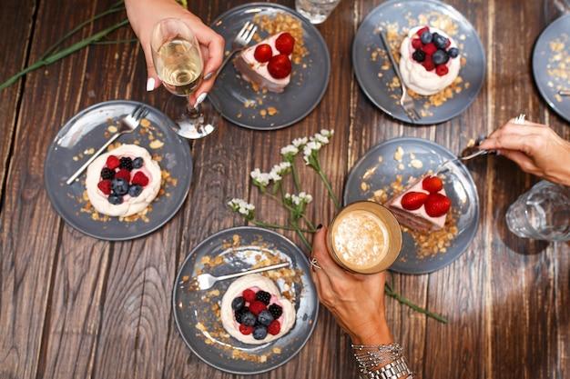 Festa de despedida de solteira, mãos de meninas com bebidas e bolos doces com frutas de verão em uma mesa de madeira. festa, mesa doce. verão oferecer sobremesas no restaurante.