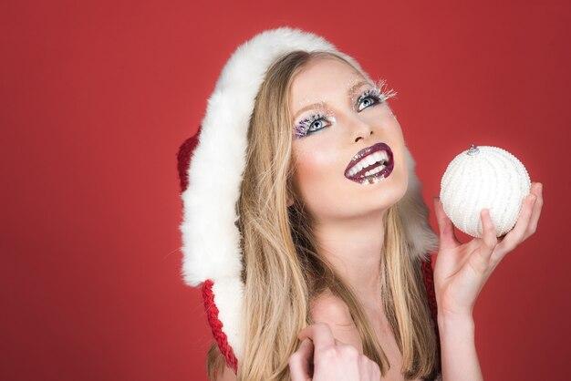 Festa de férias de inverno, natal, ano novo e conceito de celebração, mulher sorridente com chapéu de ajudante de papai noel