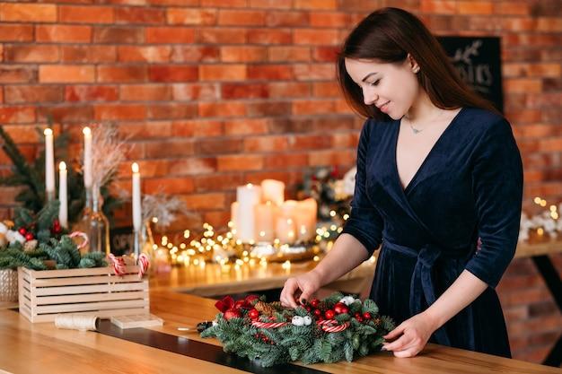 Festa de férias de inverno. senhora de vestido azul, preparando a guirlanda de natal para decorar o interior da casa.