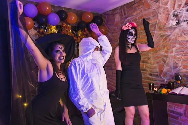 Festa de halloween em casa, grupo de amigos fantasiados se divertindo dançando