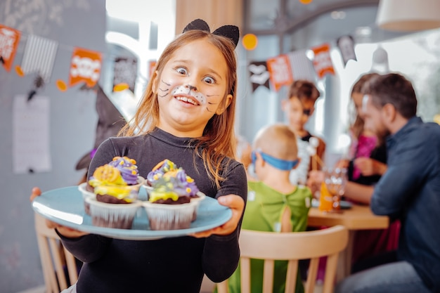 Festa de halloween. garota engraçada de olhos escuros vestindo roupa de gato na festa de halloween segurando um prato com deliciosos cupcakes brilhantes