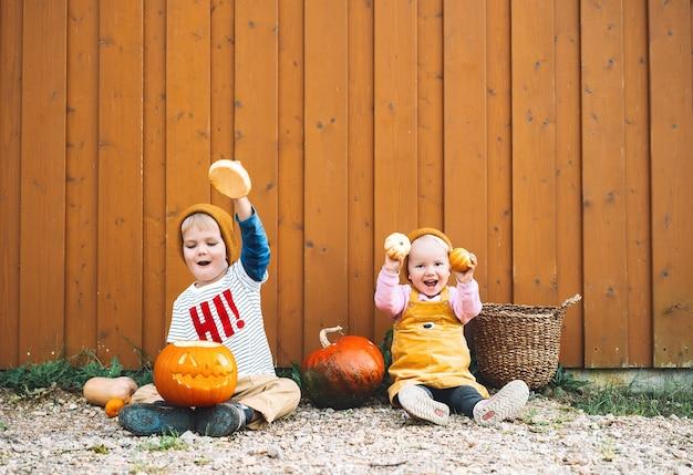 Festa de halloween para crianças crianças adoráveis com abóboras no fundo do celeiro de madeira com espaço de cópia