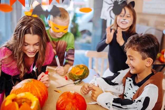 Festa de halloween. quatro crianças bonitas e radiantes participando da celebração do halloween colorindo abóboras