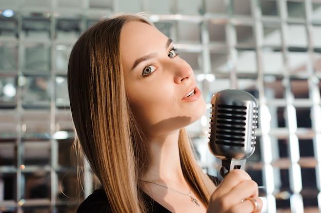 Festa de karaoke. menina de beleza com um microfone cantando. festa de discoteca. celebração.