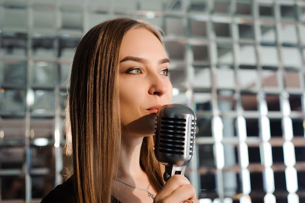 Festa de karaoke, menina de beleza com um microfone cantando