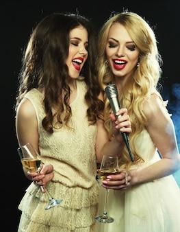 Festa de karaoke. meninas de beleza com um microfone cantando e dançando sobre fundo escuro.