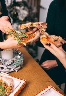 Festa de meninas com pizza, torcendo com fatias de pizza em casa, entrega de comida
