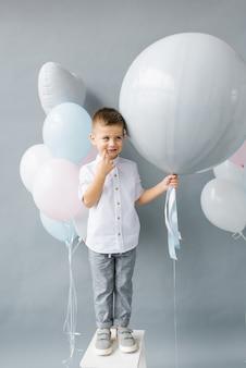 Festa de revelação de gênero uma criança de quatro anos segura um balão nas mãos para descobrir o gênero