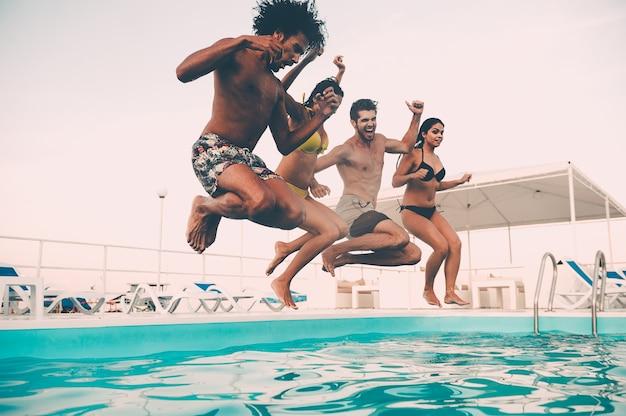 Festa de verão na piscina. grupo de jovens lindos parecendo felizes enquanto pulam na piscina juntos