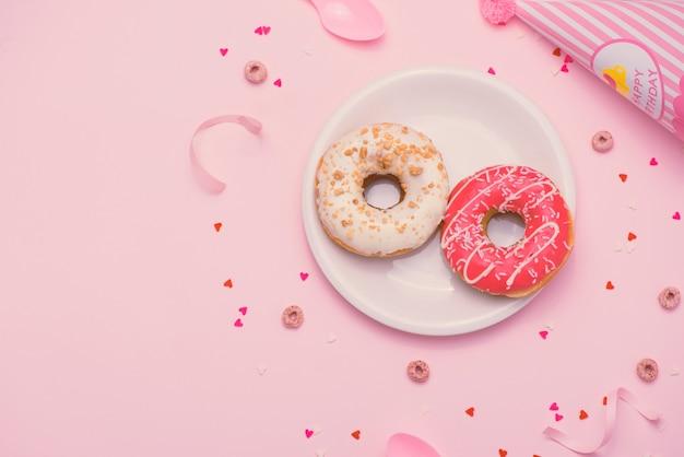 Festa. diferentes donuts redondos açucarados vitrificados coloridos e garrafas de bebidas no fundo rosa.