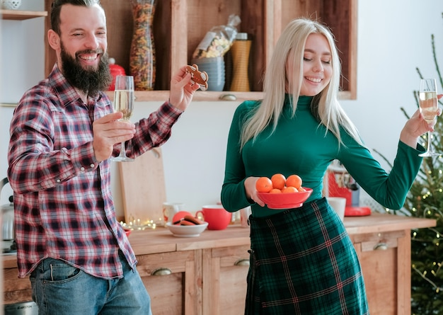 Festa divertida de natal. casal feliz dançando na cozinha com champanhe e tangerinas.