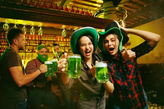 Festa do dia de são patrício. amigos felizes está comemorando e bebendo cerveja verde.